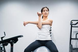 バランスボールでトレーニングする女性の写真素材 [FYI04906918]