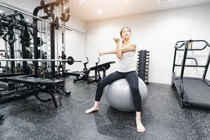 バランスボールでトレーニングする女性の写真素材 [FYI04906923]