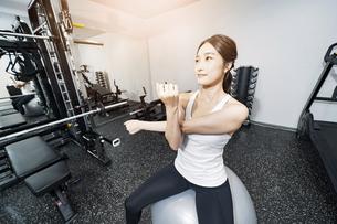 バランスボールでトレーニングする女性の写真素材 [FYI04906926]