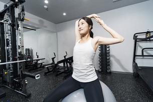バランスボールでトレーニングする女性の写真素材 [FYI04906932]