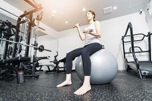 バランスボールとダンベルでトレーニングする女性の写真素材 [FYI04906935]