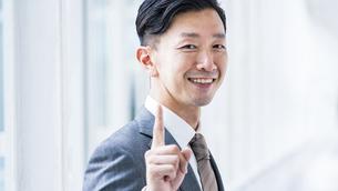 人差し指を立てるポーズをするビジネスマンの写真素材 [FYI04906954]