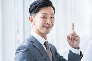 人差し指を立てるポーズをするビジネスマンの写真素材 [FYI04906955]