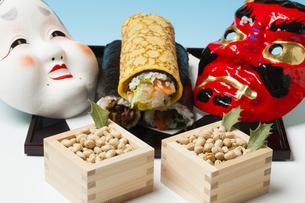 鬼とおたふくの面と大豆と恵方巻きの写真素材 [FYI04907471]