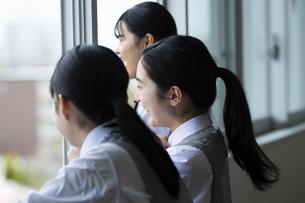 教室の窓側で雑談をする笑顔の女子校生たちの写真素材 [FYI04907738]