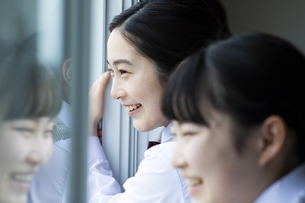 教室の窓の外を眺める笑顔の女子校生の写真素材 [FYI04907739]