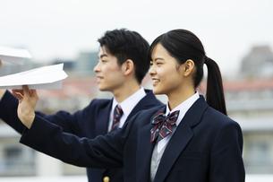 紙飛行機を飛ばす高校生の写真素材 [FYI04907782]
