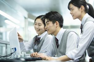 友達とパソコンを操作する男子高校生の写真素材 [FYI04907801]