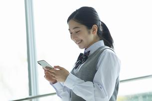 スマートフォンを見ている女子高生の写真素材 [FYI04907808]