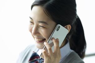 スマートフォンで友達と電話をする女子高生の写真素材 [FYI04907813]