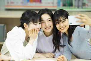 図書室で自撮りをする女子学生たちの写真素材 [FYI04907862]