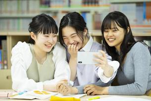 図書室で自撮りをする女子学生たちの写真素材 [FYI04907864]