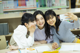 図書室で自撮りをする女子学生たちの写真素材 [FYI04907871]