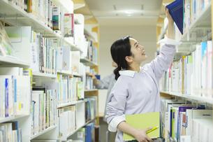 図書館で本を選ぶ女子学生の写真素材 [FYI04907872]