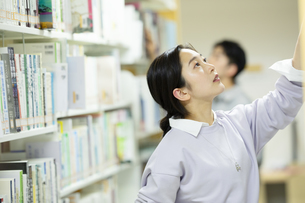 図書館で本を選ぶ女子学生の写真素材 [FYI04907878]