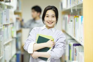 図書館で本を抱えて笑顔の女子学生の写真素材 [FYI04907880]