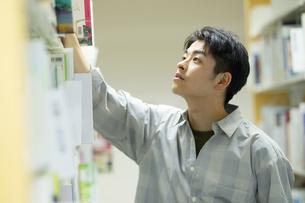 図書館で本を選ぶ男子学生の写真素材 [FYI04907892]