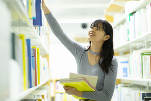 図書館で本を選ぶ女子学生の写真素材 [FYI04907902]
