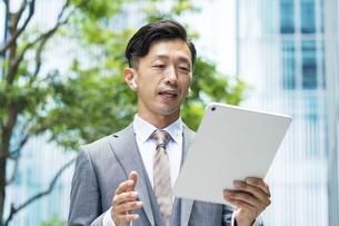 タブレットPCの画面を見るビジネスマン の写真素材 [FYI04908238]