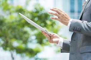 タブレットPCの画面を見るビジネスマン の写真素材 [FYI04908245]