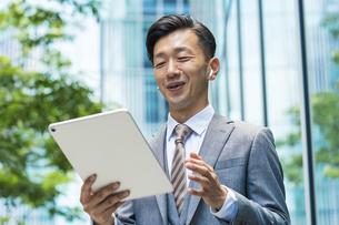 タブレットPCを使ってオンラインコミュニケーションをするビジネスマンの写真素材 [FYI04908249]