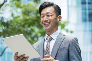 タブレットPCを使ってオンラインコミュニケーションをするビジネスマンの写真素材 [FYI04908251]