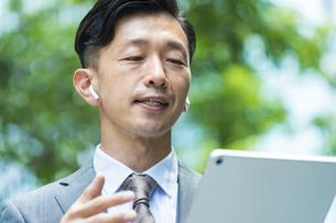 タブレットPCを使ってオンラインコミュニケーションをするビジネスマンの写真素材 [FYI04908255]