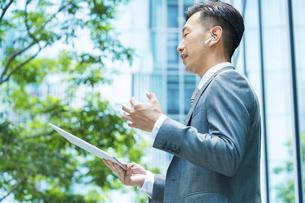 タブレットPCを使ってオンラインコミュニケーションをするビジネスマンの写真素材 [FYI04908258]