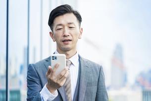 スマートフォンの画面を見る男性の写真素材 [FYI04908262]