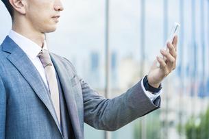 スマートフォンを持つスーツ姿の男性の手の写真素材 [FYI04908269]