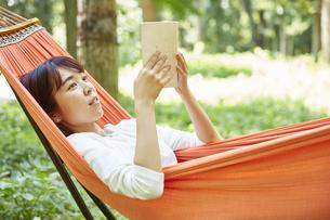 ハンモックに寝転んで本を読む女性の写真素材 [FYI04908358]