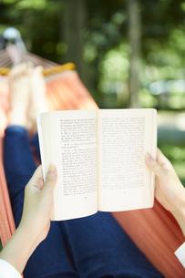 ハンモックに寝転んで本を読む女性の手元の写真素材 [FYI04908359]