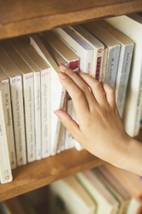 本棚にの本を取ろうとする女性の手元の写真素材 [FYI04908376]
