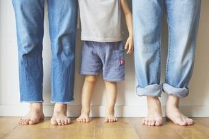 壁前に並んだ家族3人の足元の写真素材 [FYI04908412]