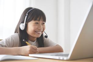ダイニングでオンライン学習をする女の子の写真素材 [FYI04908421]