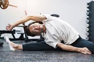 ジムでストレッチ運動をする男性の写真素材 [FYI04908451]
