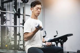 ダンベルを使って筋トレをする中年男性の写真素材 [FYI04908542]