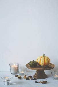 白壁前に飾られたカボチャとキャンドルの写真素材 [FYI04908613]