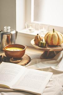 窓辺に飾ってあるカボチャとスープと本の写真素材 [FYI04908701]