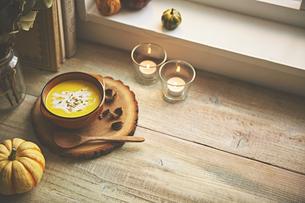 窓辺に置いてあるカボチャのスープの写真素材 [FYI04908703]