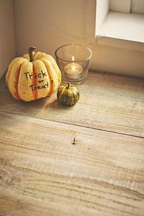 窓辺の端に飾ってあるカボチャとキャンドルの写真素材 [FYI04908708]