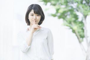 「秘密」のハンドサインをする若い女性の写真素材 [FYI04909457]