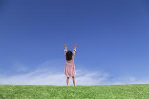 青空を背景にした草地の地平線で両手を上げ希望と喜びを表現する少女の後ろ姿の写真素材 [FYI04910374]