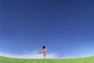 青空を背景にした草地の地平線で喜びを表現するポーズをする少女の後ろ姿の写真素材 [FYI04910377]