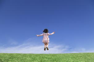 青空を背景にした草地の地平線でジャンプをして喜びを表現する少女の後ろ姿の写真素材 [FYI04910378]
