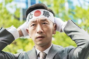 「必勝」のハチマキを頭に巻くスーツ姿の男性の写真素材 [FYI04910724]
