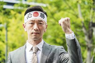 「必勝」の鉢巻を巻いてガッツポーズする男性 の写真素材 [FYI04910735]