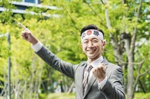 「必勝」の鉢巻を巻いて手を上げる男性の写真素材 [FYI04910740]