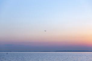 遠くに飛行機が飛んでいる東京湾の夕景の写真素材 [FYI04910793]
