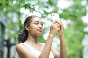 スマートフォンを操作するビジネスウーマンの写真素材 [FYI04911145]